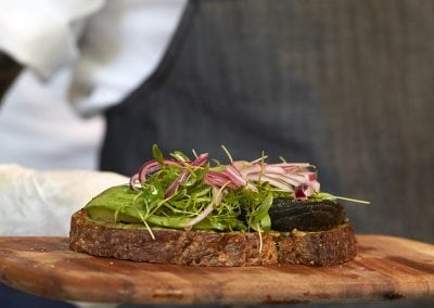 A server holding a wooden plate with a bread slice with salad on top