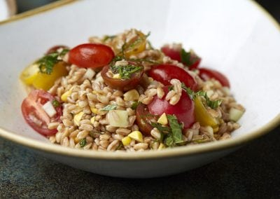 A bowl of quinoa salad with cherry tomatos