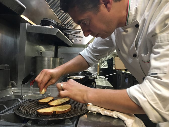 Our executive chef Roberto Bearzi on the kitchen preparing a plate